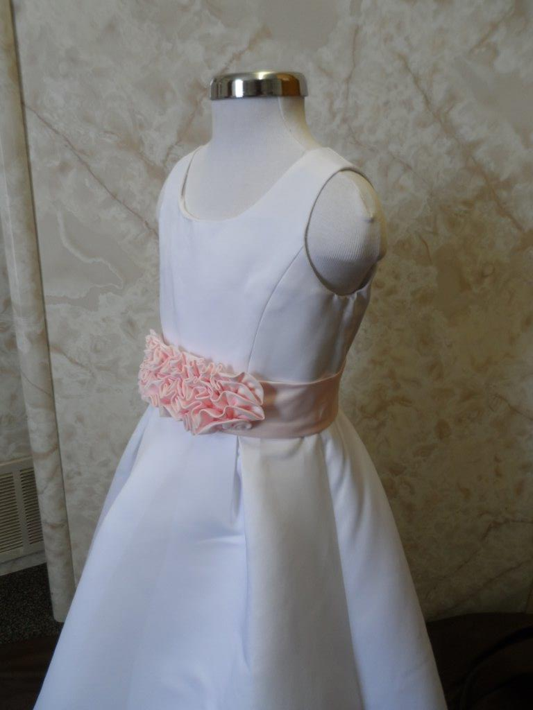 Ivory or White long dress with attractive pink cummerbund sash and ruffled bow accent.
