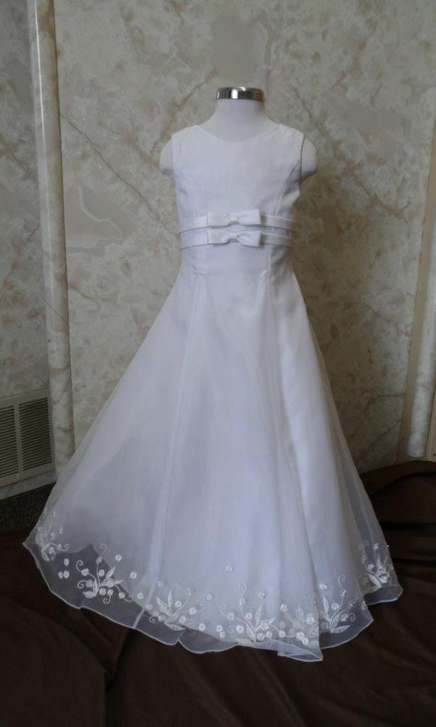 Long Sleeveless white flower girl dress with double bow waist, sheer overlay and floral embroidered hemline, on sale.
