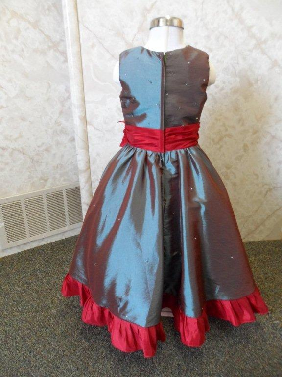 teal dress with apple red sash and ruffled hemline